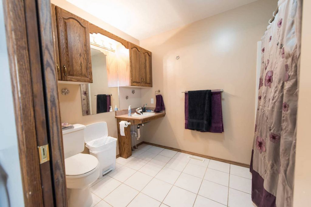 The sink in this bathroom has been set at a height that works for the homeowner, and has no cabinetry underneath. The tap is levered, and easy to access. The toilet is taller than standard, and the tile flooring is easy to roll on, and easy to clean, although grout stains are an issue.