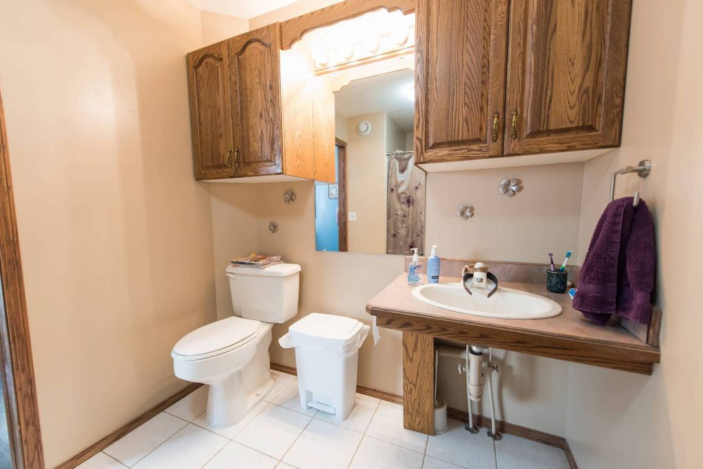 There is a lot of space between the toilet and sink for maneuverability. The cabinets are too high for the homeowner to access, which could be fixed by moving the sink into the corner and adding a shallow pantry.
