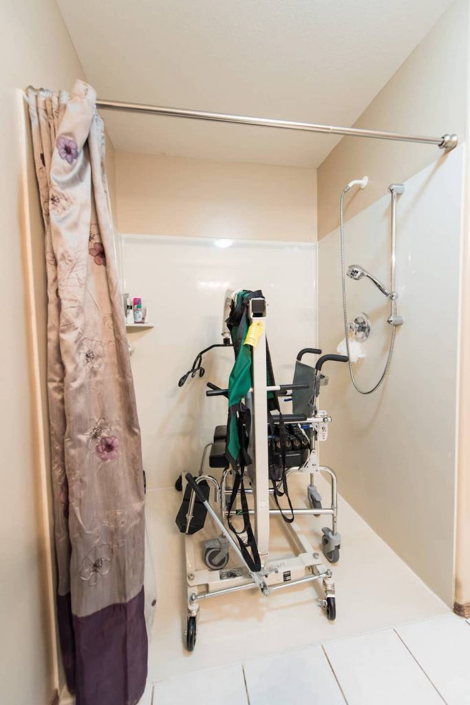 This shower was built large enough to house a shower chair, as well as a manual lift, allowing for items to be hidden when not in use. The shower is a molded unit which slopes very slightly from all sides to the drain, allowing the stall to be level with the tile flooring - no lip!