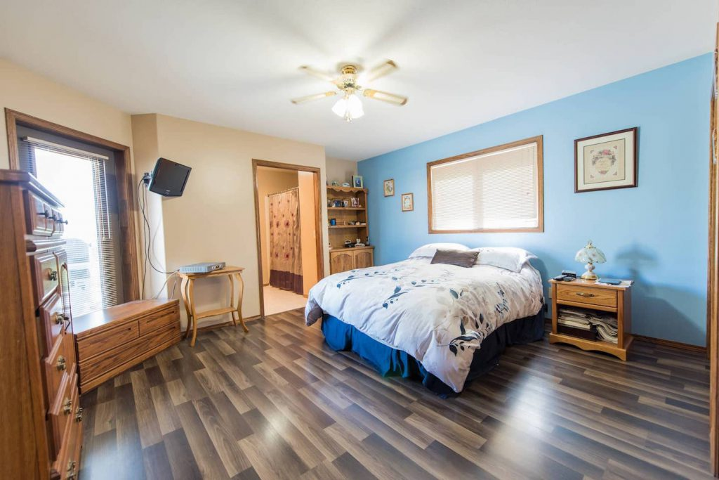 Laminate flooring is great for wheeling on and keeping clean. The transition to the ceramic bathroom tile is a slightly rounded piece that matches the laminate, and does not cause any issues for the homeowner to wheel over.  The pocket door, which separates bed and bathroom allows for more room, and greater accessibility, although if pushed in all the way it can be difficult to open.