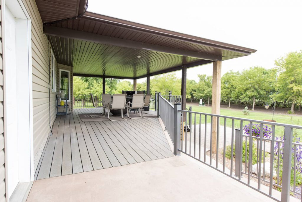 The large composite back deck meets up with a concrete ramp that extends around the side of the house.
