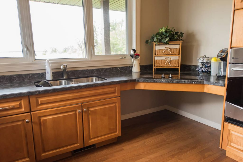 The homeowner has chosen to not lose storage space under the sink, and instead sits sideways while using it.  One regret is having the dishwasher placed too far away from the sink.