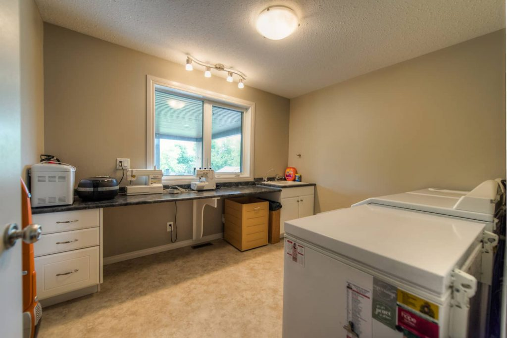The laundry / sewing room has an accessible folding area that doubles as a sewing table. Front load washer and dryer work well for laundry tasks.