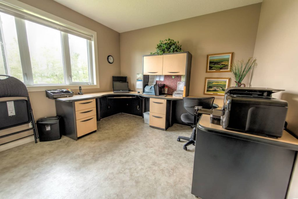 The office area is floored in laminate, and has a wraparound desk with a large naneuverable area underneath, as well as a second desk. Low windows add light and view.