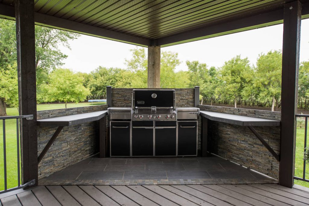 The bbq is angled into the corner of the deck, and the homeowners have built open countertops to make getting food on and off the bbq easier, creating an accessible workspace.
