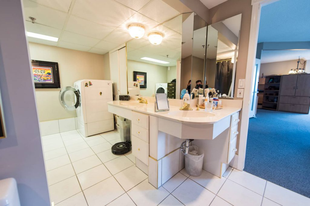 The laundry room and bathroom are one large unit. A wheel under sink/countertop is separated by a row of storage drawers.