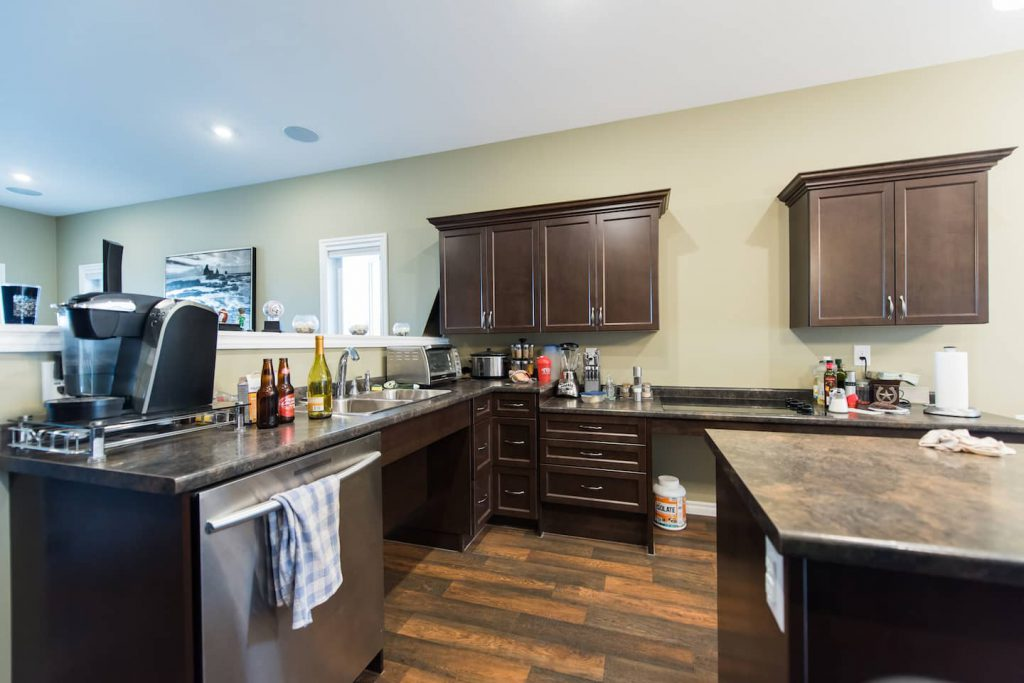 This kitchen features vinyl plank flooring, which runs throughout most of the home. The wheel under sink and stovetop make kitchen chores easy.