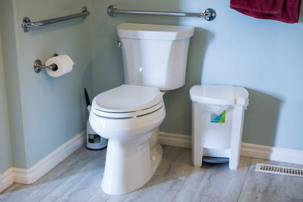 The raised toilet is at a height to make transfers easier. Grab bars behind and to the side of the toilet assist in safe transfers.