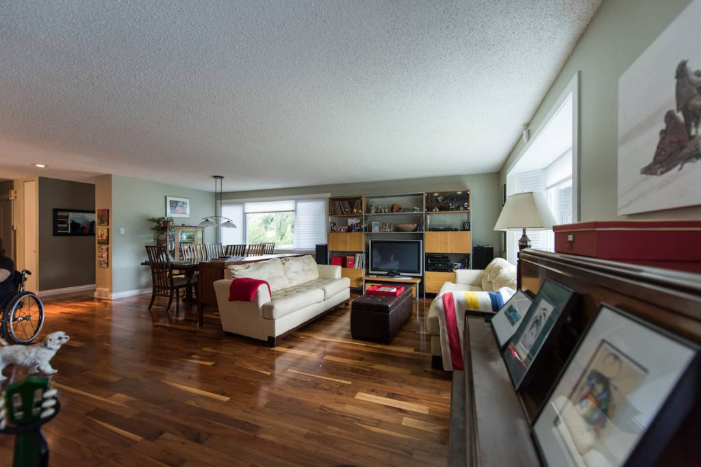 The open living room provides a lot of space for maneuverability. Hardwood floors offer easy wheeling, and leather furniture helps make transfers easier.