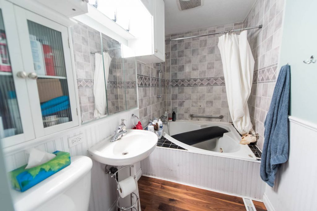 The home renovators have made great use of limited space by incorporating a bath bench, adjustable height shower, and pedestal sink. Flooring is hardwood, and as it is throughout the house there is no transition.