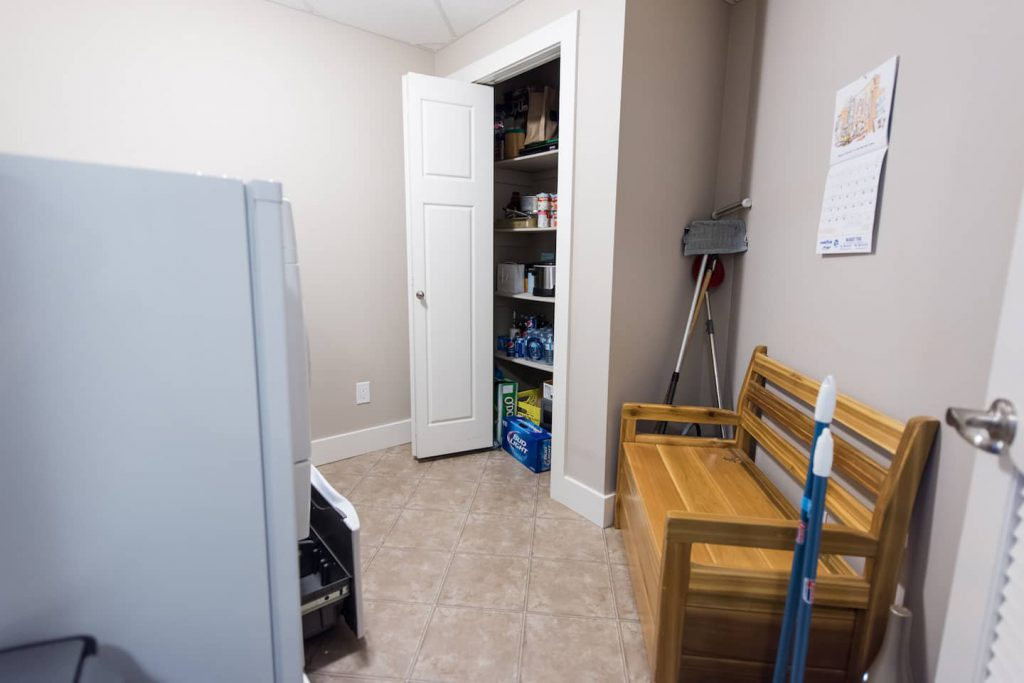 The laundry room has laminate flooring, side by side front load washer and dryer, and a storage closet.