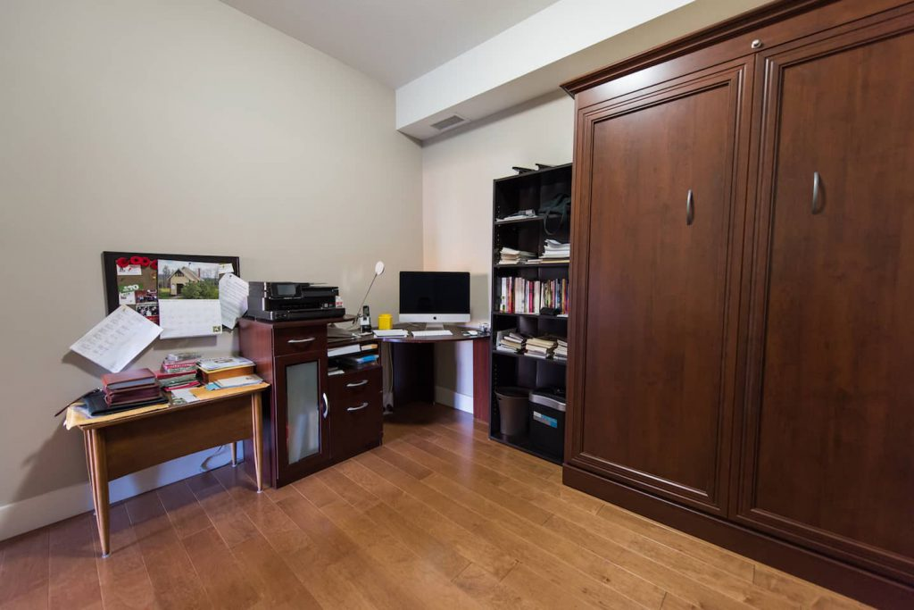 The desk is smaller than many, but works well for access for the homeowner. The large chest encases a Murphy bed, which folds up when not in use, creating extra space.