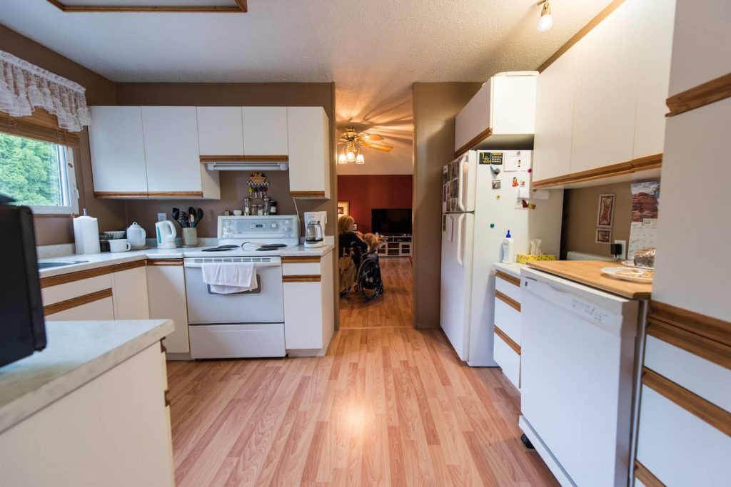 The kitchen is open enough for maneuverability, but does not have many features specific to accessibility. Laminate floor runs through from kitchen, to dining, to living room areas.