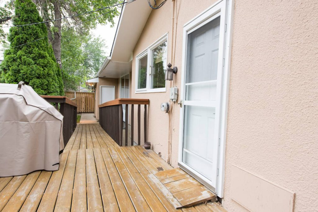 A wooden wedge ramps the deck to the back door.