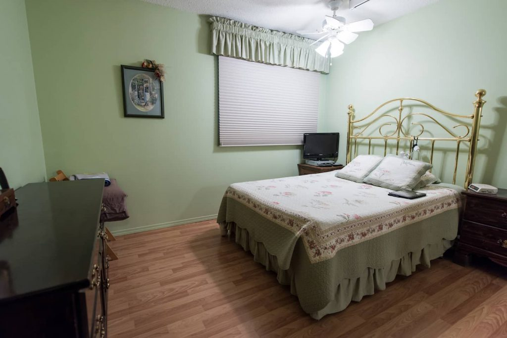 The bedroom features laminate flooring, and a ceiling fan that works by remote control.
