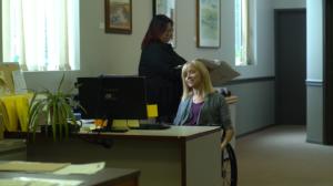 Women using wheelchair at office desk