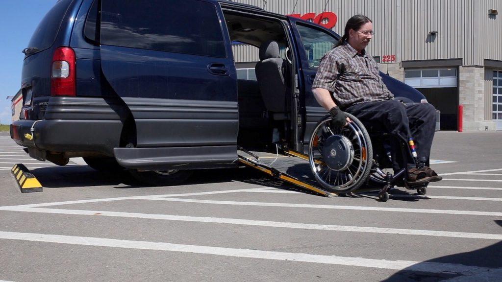 Man using wheelchair exiting minivan ramp